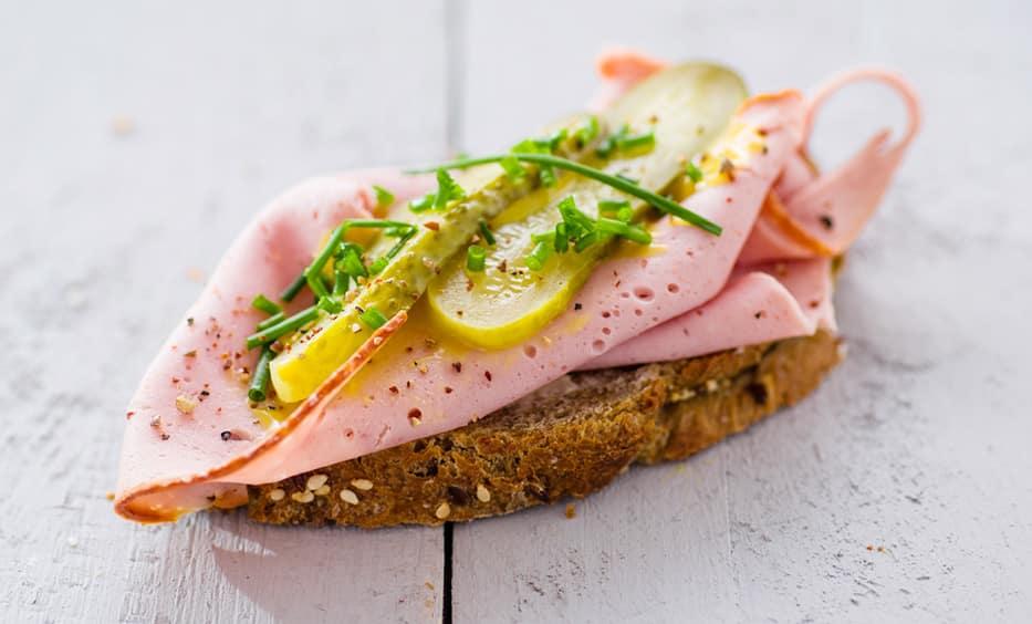 Honigsenf, Leberkäs, Essiggurke, Röstzwiebeln, Schnittlauch, Salz & Pfeffer